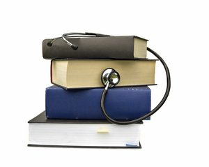 Studying Medicine or Research Book with Stethoscope on White